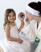 Mother applying blusher with her daughter — Foto Stock