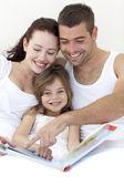 Yatakta ailesiyle okuma bir kız portresi — Stok fotoğraf