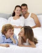 Bror och syster tittar på varandra i sängen med sina föräldrar — Stockfoto