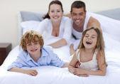 Broer en zus plezier in bed met hun ouders — Stockfoto
