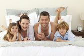 Familia tumbado en la cama con el pijama — Foto de Stock