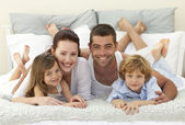 Happy family lying in bed and smiling at the camera — Stock Photo