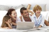 Familia feliz en la cama usando una laptop — Foto de Stock
