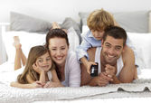 Family lying in bed watching television — Stock Photo