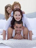 Portret van gelukkige ouders en kinderen plezier in bed — Stockfoto