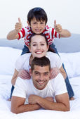 Happy parents and son in bed with thumbs up — Stock Photo