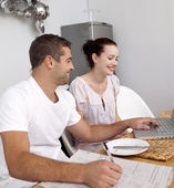 Couple working with a laptop in kitchen — Stock Photo