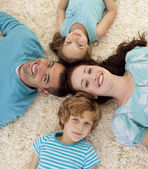 Happy family on floor with heads together — Stock Photo