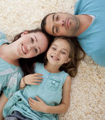 Portrait of parents and daughter on floor with heads together — Stock Photo