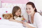 Sick little girl in bed taking cough medicine — Stock Photo