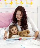 Anne ve kızı yatakta okuma — Stok fotoğraf