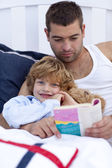 Little son reading with his father in bed — Stock Photo