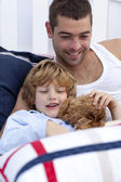 Portrait of father and son reading a book in bed — Stock Photo
