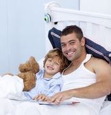 Smiling father and son reading a book in bed — Stock Photo