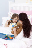 Woman and little girl playing with a stethoscope — Stock Photo
