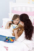 Mother and sick daughter playing with a stethoscope — Stock Photo