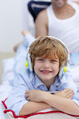 Portrait of a little boy listening to music in bedroom — Stock Photo