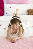 Little girl on headphones listening to the music in bed — Stock Photo