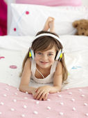 Little girl listening to the music in bed — Stock Photo