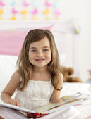 Little girl reading in bed — Stock Photo