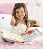 Happy little girl reading in bed with thumb up — Stock Photo