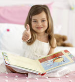 Little girl reading in bed with thumb up — Stock Photo