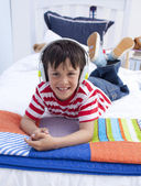 Portrait of boy on headphones listening to music in bed — Stockfoto