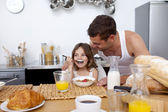 Daughter eating cereals and fruit for breakfast — Stock Photo