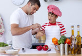 Boy hurt his finger cooking and father treating it — Stock Photo