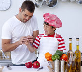 Boy cut his finger in kitchen and father treating it — Stock Photo