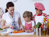 Children helping mother cooking in the kitchen — Stock Photo