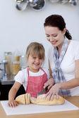母娘にパンをカットする方法を教える — ストック写真
