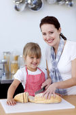 Ler mor och dotter skära bröd — Stockfoto