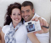 Portrait of couple playing with digital camera — Stock Photo