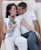 Lovers on sofa with a rose — Stock Photo