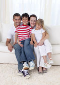 Smiling family sitting on sofa together — Stock Photo