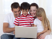 Family at home playing with a laptop — Stock Photo
