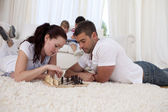 Couple playing chess on floor in living-room — Stock Photo