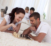 Smiling couple playing chess on floor in living-room — Stock Photo