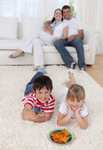 Brother and sister watching television on floor in living-room — Stock Photo