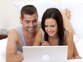 Couple in bed using a laptop — Stok fotoğraf