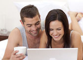 Couple in bed having fun with a laptop — Stock Photo