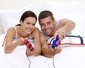 Couple having fun playing videogames in bed — Stock Photo