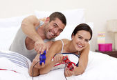 Husband and wife playing videogames in bed — Stock Photo