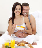 Wife and husband having nutritive breakfast in bed — Stock Photo