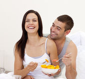Smiling couple having nutritive breakfast in bed — Stock Photo
