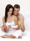Couple having nutritive breakfast sitting in bed — Stock Photo