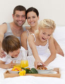 Family eating breakfast in bedroom — Stock Photo