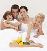Happy family having breakfast in bedroom — Stock Photo