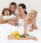 Family having breakfast in bed in the morning — Stock Photo